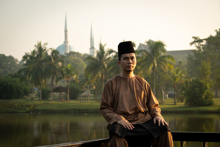 Portrait of man wearing traditional clothing while sitting on railing against lake during sunset