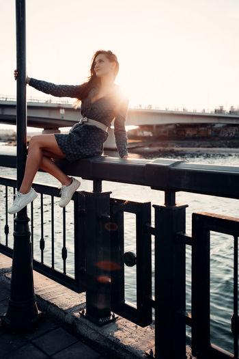 Woman on railing against sky