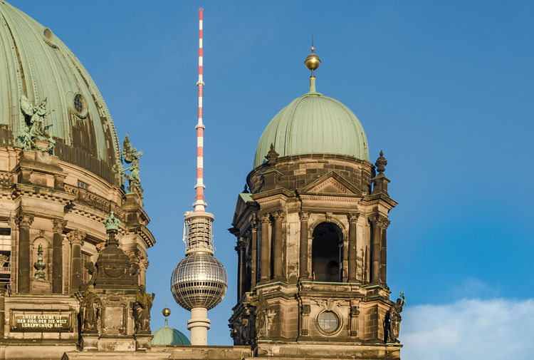 Low angle view of berlin cathedral and fernsehturm against sky in city