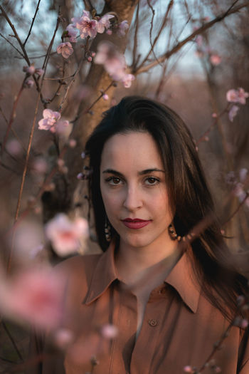 Portrait of beautiful woman with pink flower