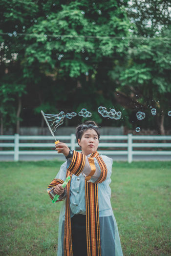 Woman in traditional clothing making bubbles while standing on field