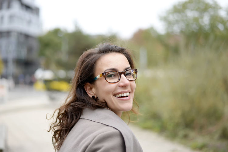 happy businesswoman Beautiful Beauty Business Businesswoman Cheerful City Coat Confident  Contentment Day Eyeglasses  Glasses Happiness Happy Laughing Livestyle Manager One Person Outdoors Portrait Smiling Successful Urban Woman Young Women