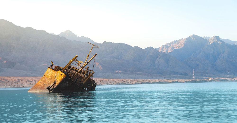 Abandoned ship in sea against mountain range