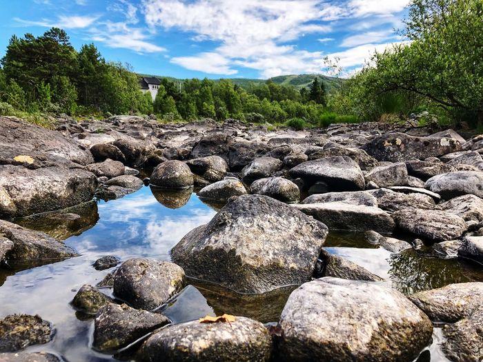 Rocks by stream against sky