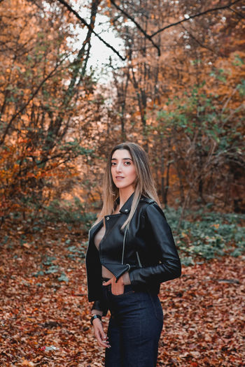Portrait of beautiful young woman standing on street during autumn