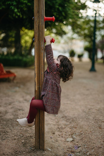 Side view of girl playing with umbrella
