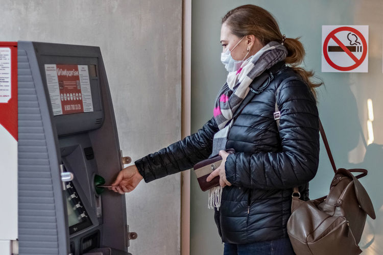 Side view of woman wearing mask using atm