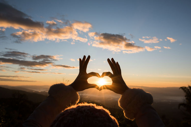 Silhouette hands making heart shape against sky during sunset