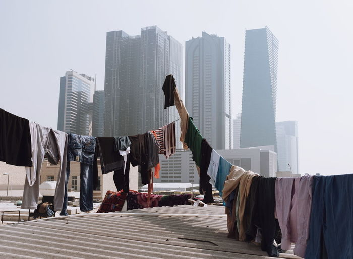 Clothes drying against modern buildings in city against sky