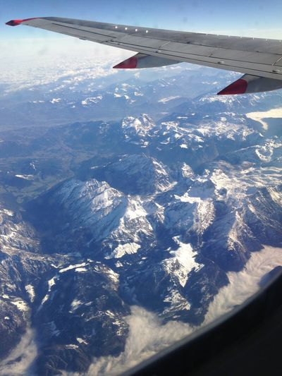 Aerial view of airplane flying over snowcapped landscape