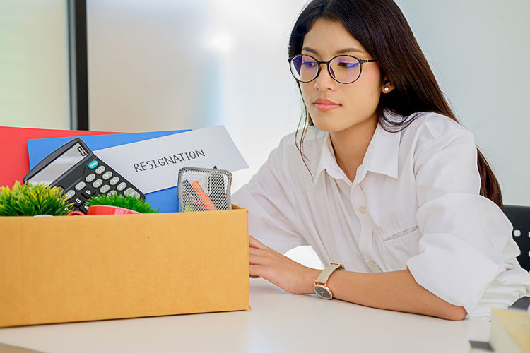 Woman With Objects Sitting At Desk In Office