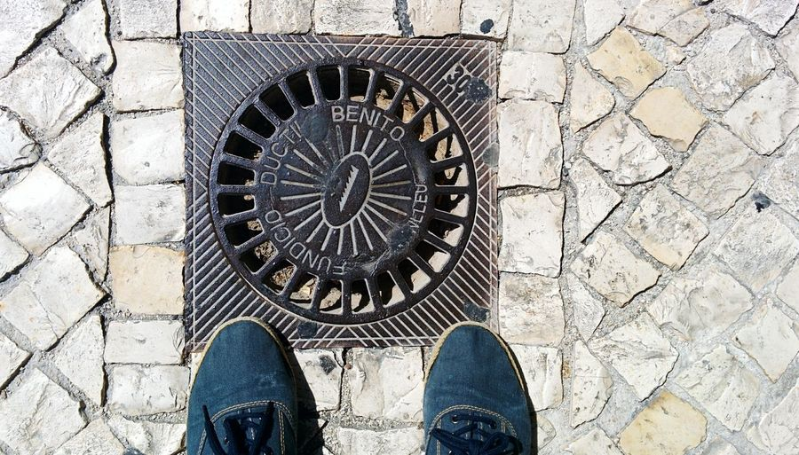 Low section of person standing by drain
