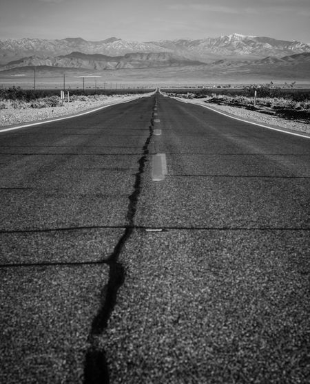Cracked Road Leading Towards Mountains