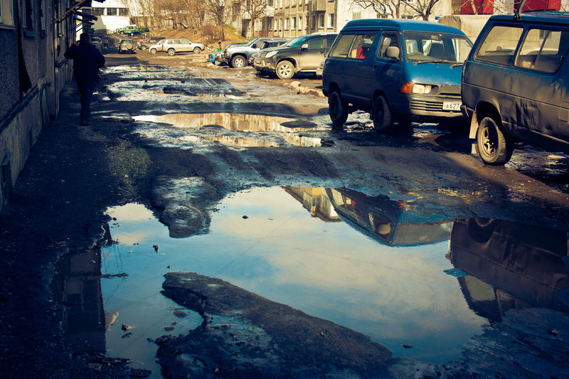 Reflection of city in puddle on road in winter