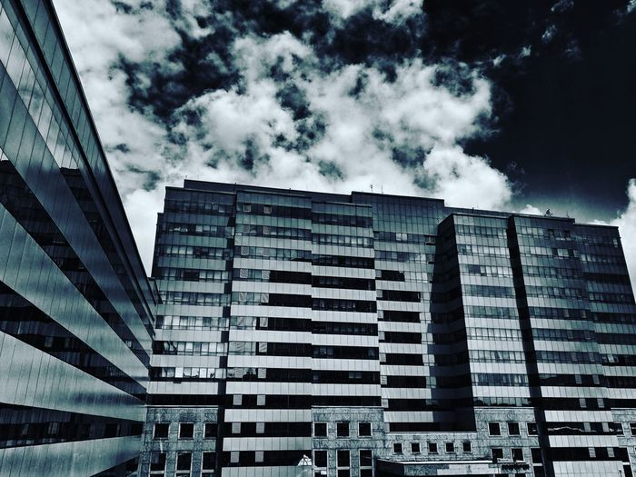 Clouds over a building in an IT Park in Bangalore, IndiaArchitecture Built Structure Building Exterior Low Angle View City Modern Outdoors Day No People India It Park Tech Park Skyscraper Cloud - Sky Sky Bangalore Urban Skyline Monochrome Clouds