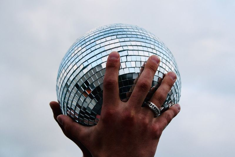Close-up of hands holding disco ball against sky