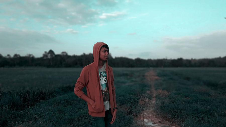 Man in hood clothing standing on field against sky