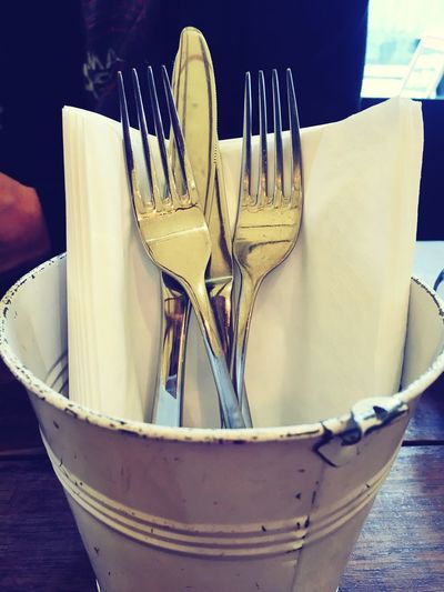 Close-up of cutlery in metal bucket on table