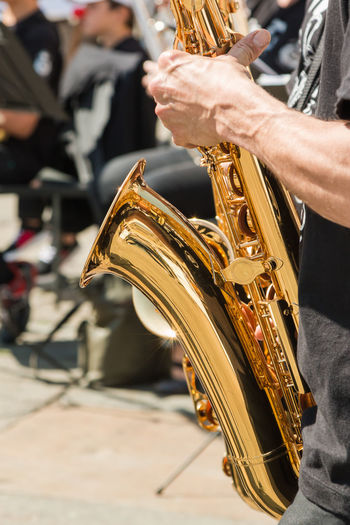 Midsection of man playing trumpet in city