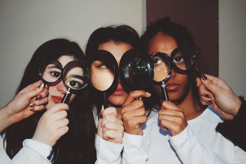 Close-up of young friends looking through magnifying glass