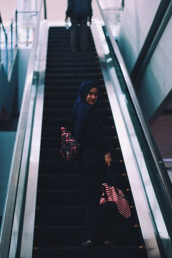 Low Angle View Of Woman Wearing Hijab Standing On Escalator