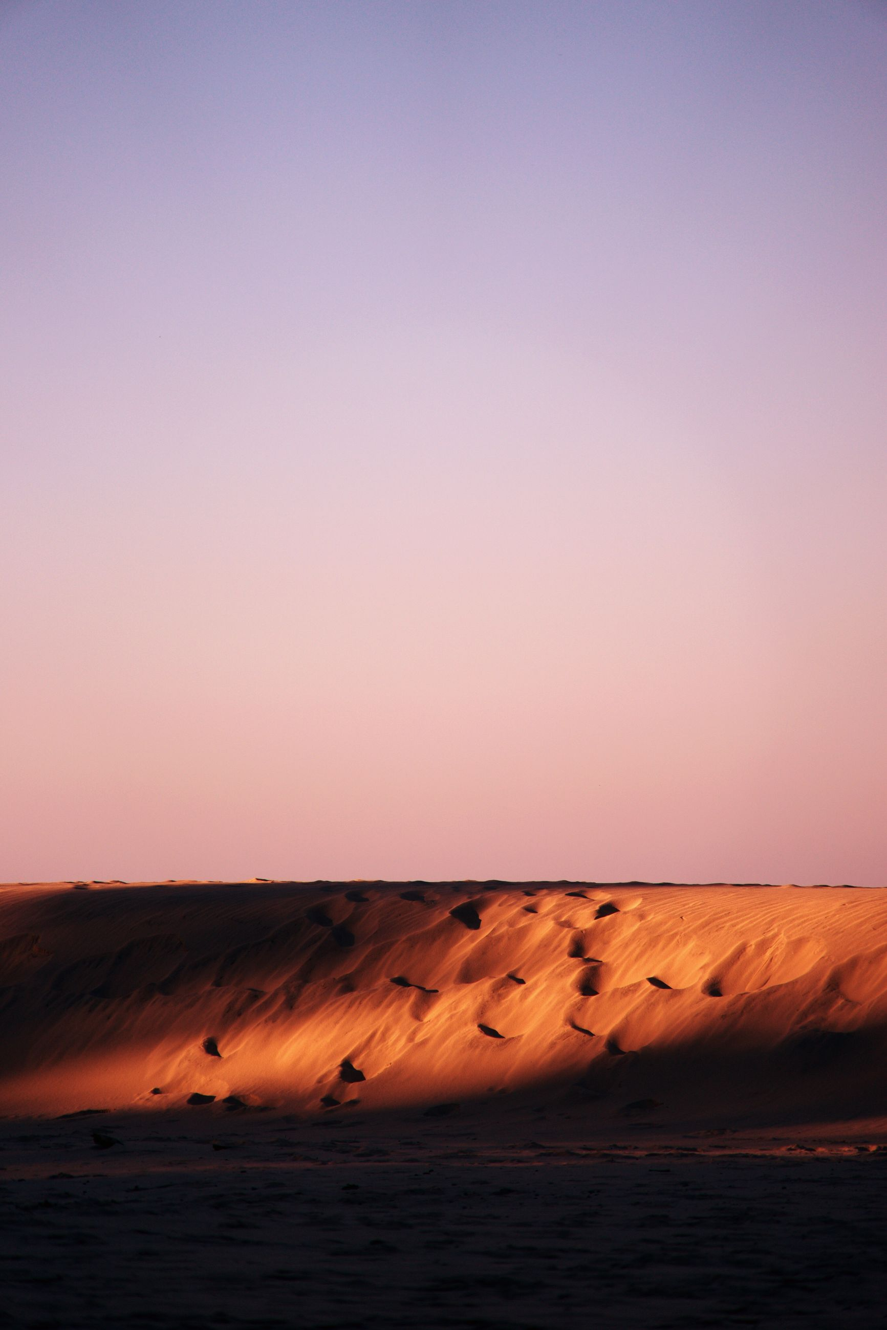 sand, desert, landscape, nature, sunset, tranquil scene, scenics, tranquility, no people, beauty in nature, outdoors, pink color, clear sky, arid climate, horizon over water, sand dune, beach, day