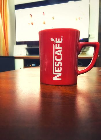 Nescafé Cup Mug Indoors  Food And Drink Table Drink Red No People Text Still Life Coffee Cup Refreshment Western Script Close-up Communication Coffee Tea Coffee - Drink Focus On Foreground Tea Cup