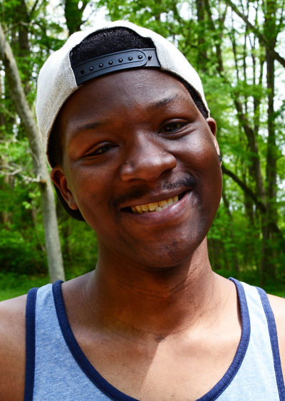 Close-up portrait of smiling young man in forest