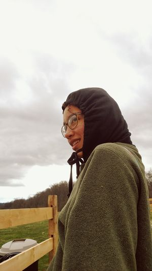 Smiling young woman wearing warm clothing while standing against cloudy sky