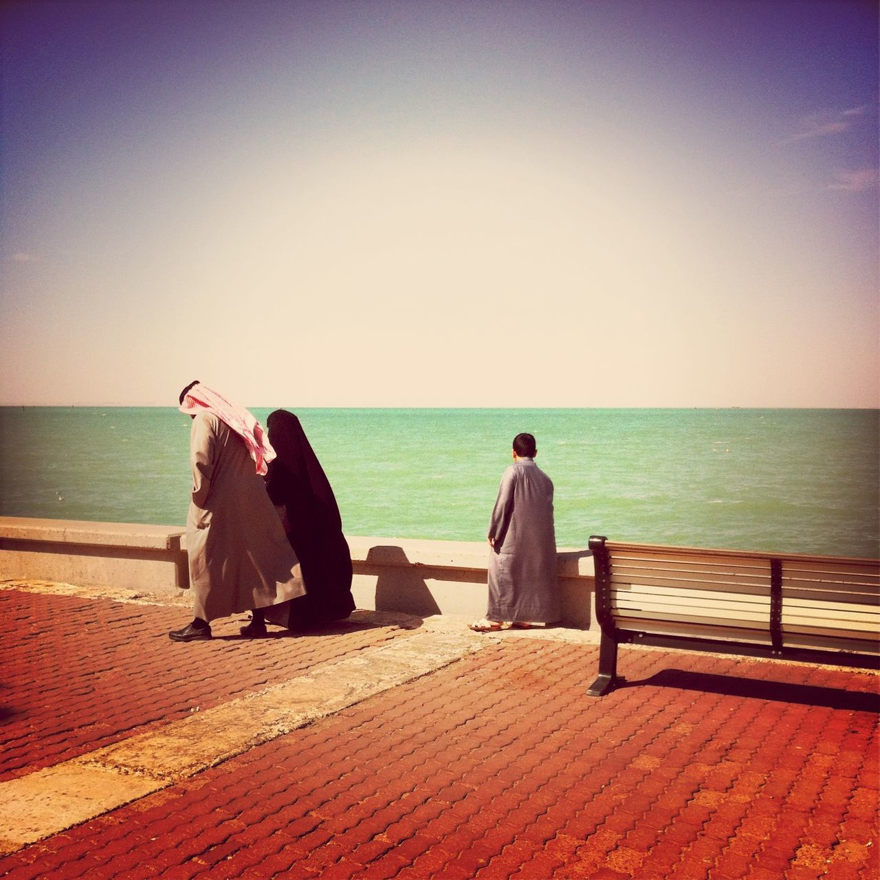 Arab family walking on cobbled lane against the sea