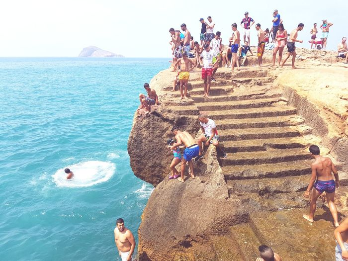 Large Group Of People Beach Cliffs And Water CliffJumping Men People Sand Outdoors Vacations Crowd Sea Women Adult Day Sky Nature Water Adults Only Only Men