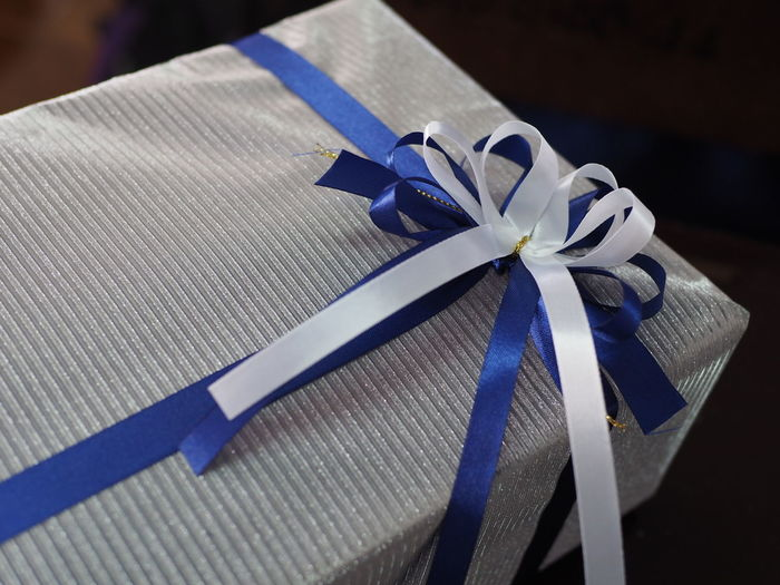 Close-up of gift with white and blue ribbon