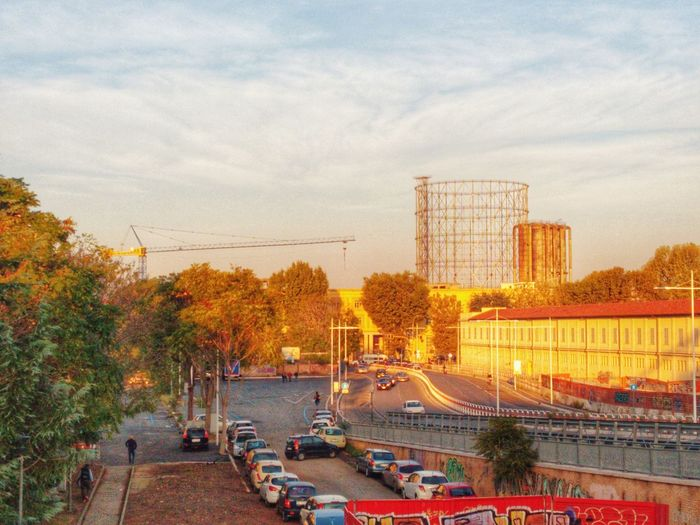 Gasometer In City At Sunrise Tree Architecture Built Structure Sky Plant Transportation Cloud - Sky Nature Mode Of Transportation Building Exterior City Outdoors No People Street Bridge Road Water Day Motor Vehicle Connection Rome Italy Roma Italia Garbatella Sunset