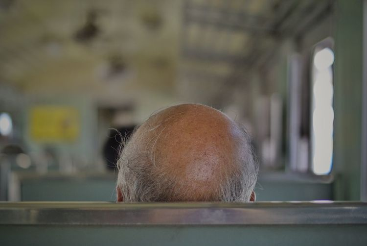 High Section Of Mature Man With Bald Travelling In Train