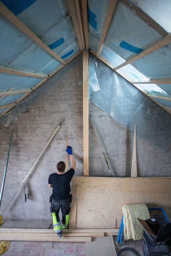 Full length rear view of man working on ceiling