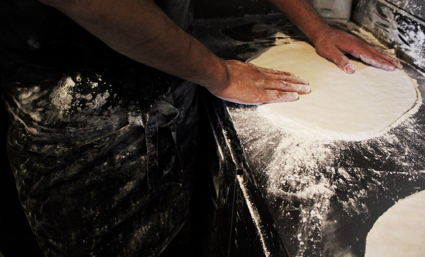 Midsection Of Chef Spreading Dough At Commercial Kitchen
