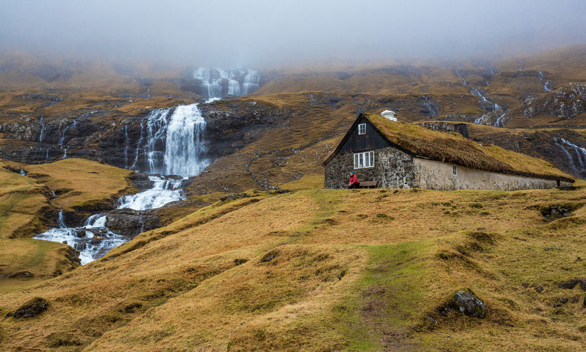 Fog Misty Waterfall One Person Outdoors Plant Architecture Travel Water Built Structure Non-urban Scene Solid Land Rock - Object Rock Landscape Beauty In Nature Day Nature Mountain Scenics - Nature Environment Faroe Islands
