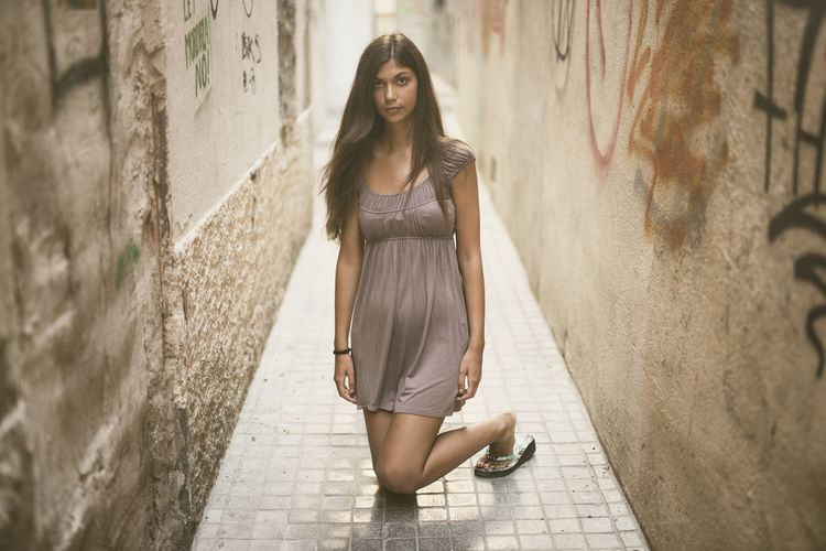 Young woman standing on wall