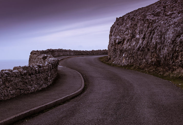 Winding coastal road Road The Way Forward Direction Sky Rock Nature Transportation Tranquil Scene Rock - Object No People Tranquility Scenics - Nature Solid Beauty In Nature Day Mountain Non-urban Scene Rock Formation Land Outdoors Formation