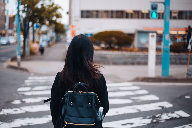 Backpack Crossing Road Day Hair Long Hair One Person Outdoors People Real People Rear View Traffic Traffic Lights Waiting Wind Women Young Adult Zebra Crossing
