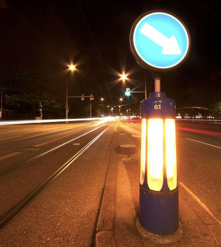 Arrow Symbol Amidst Road At Night