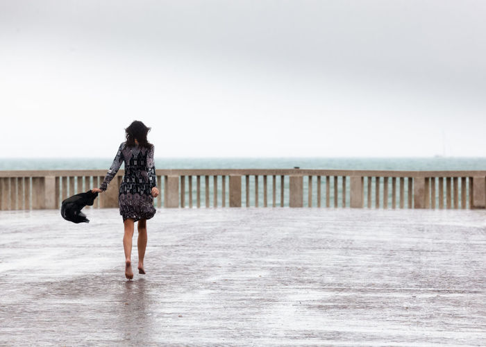 Rear view of woman walking on promenade at beach against clear sky