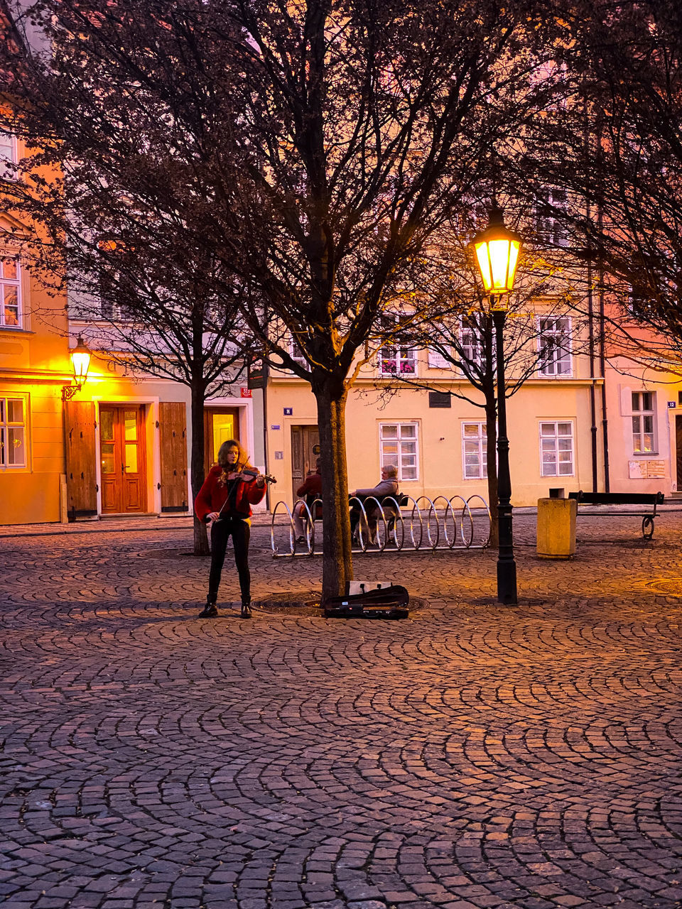 WOMAN WALKING ON STREET BY ILLUMINATED BUILDING
