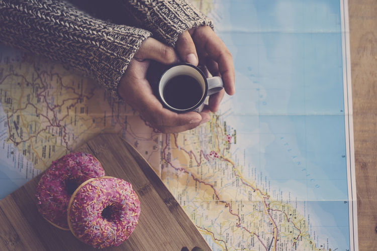 Planning a travel or adventure during the breakfast. Coffee espresso cup and donut Food And Drink Drink Cup One Person Mug Table Refreshment Coffee Coffee - Drink Holding Real People Coffee Cup Human Hand Freshness Hand Indoors  Lifestyles Food High Angle View Non-alcoholic Beverage Tea Cup Floral Pattern Snack Sweet Food Express Espresso Machine Donut Pink Color Sea Vacations Holiday Wood Backgrounds Happiness