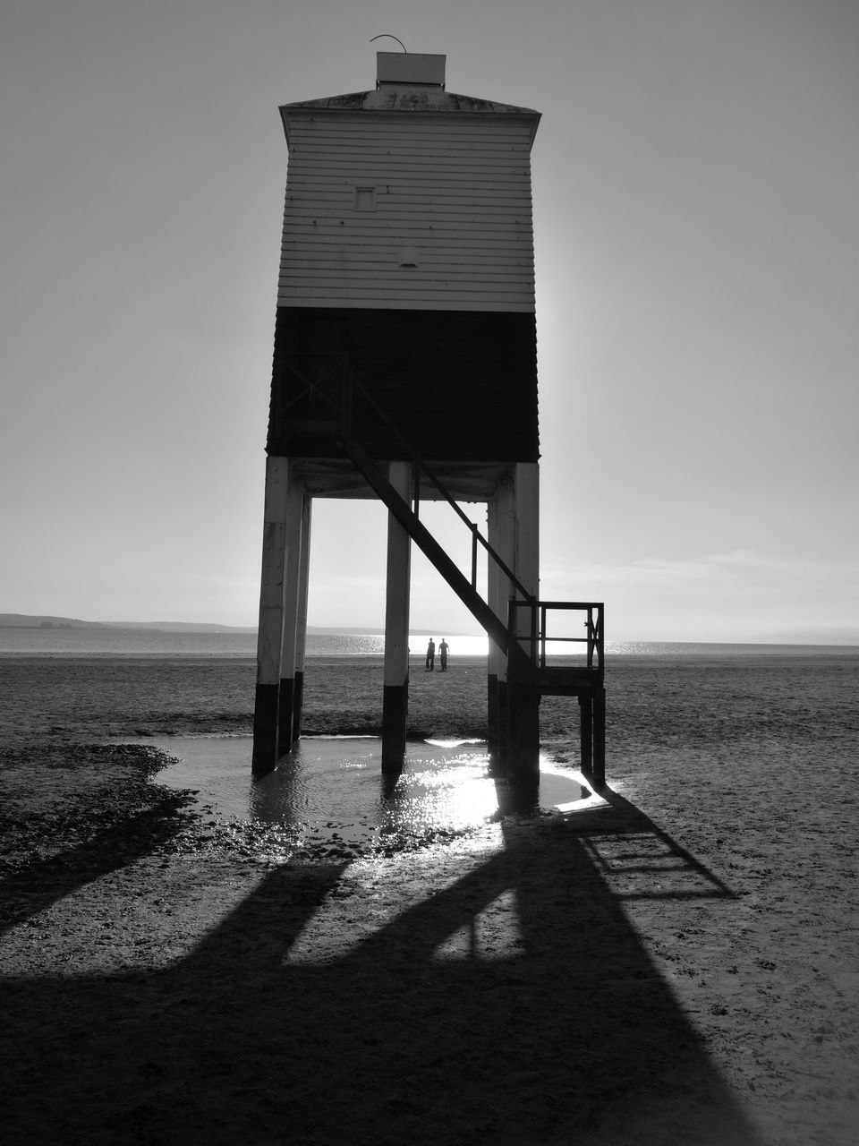 beach, sea, sand, horizon over water, shadow, built structure, no people, architecture, water, nature, tranquil scene, tranquility, scenics, sunlight, outdoors, lifeguard hut, day, clear sky, sky, beauty in nature