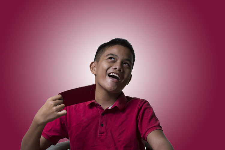 Smiling Boy Holding Card While Sitting Against Pink Background