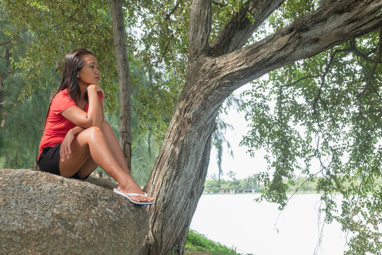 Woman sitting on tree trunk against plants