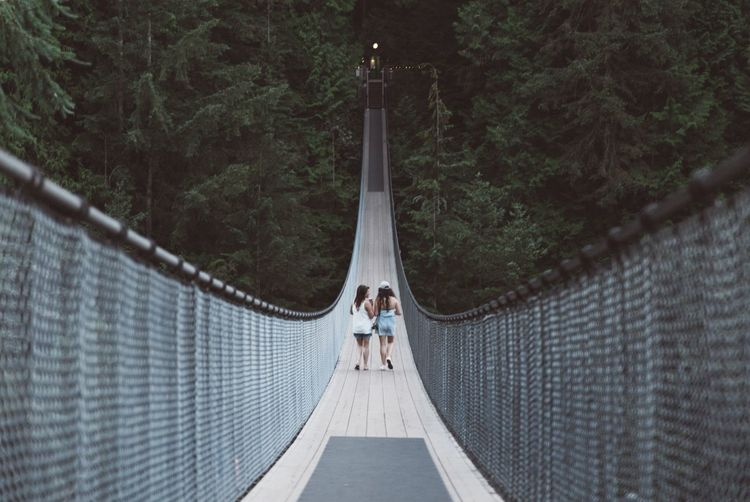 Women walking on rope bridge