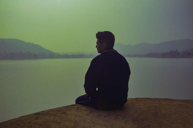 Man looking at lake against mountain range
