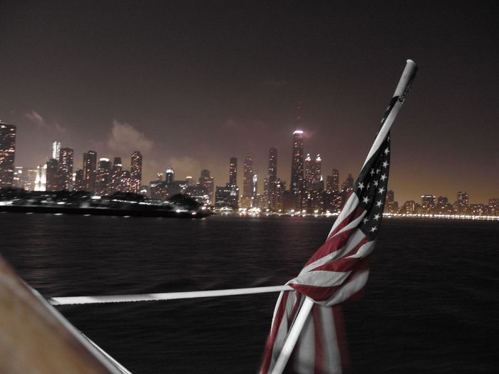 American flag against illuminated skyline